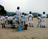 Baseball Team. A children baseball team watching to the match from the substitutes bench Royalty Free Stock Photography