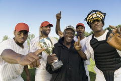 Baseball Team And Coach With Trophy Celebrating Victory. Portrait of baseball team and coach with trophy celebrating victory outdoors stock image