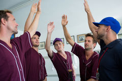 Baseball team doing high five with coach. While standing at locker room royalty free stock photo
