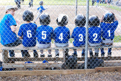 Baseball team in numerical order.. Baseball team sitting on bench with their uniform numbers in numerical order Stock Photo