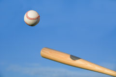 Baseball about to be struck by baseball bat. With blue sky background. Lots of copy space available for adding your own text Stock Photography