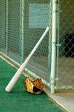 Baseball Tools. Bat and glove sit besides fence at baseball field Royalty Free Stock Photo