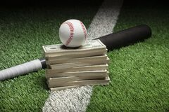 Baseball on top of stack of money with bat on green field with stripe