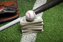 Baseball on top of stack of money with mitt and bat on green field with stripe