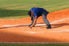 Baseball Umpire. Dusting off dirt from home plate with a brush in mid-afternoon Stock Photo