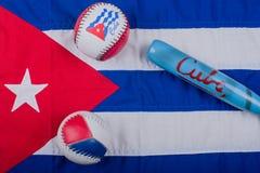 Baseball und Baseballschläger auf einer Flagge von Kuba lizenzfreies stockbild