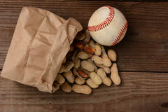 Baseball und eine Tasche mit den Erdnüssen, die heraus verschüttet werden Stockfotografie