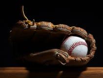 Baseball und Handschuh auf einer Bank. Stockbilder