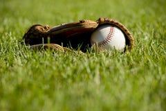 Baseball und Handschuh auf Gras lizenzfreies stockbild