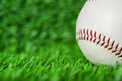 Baseball used put on green grass background. Sport game macro shot stock photo