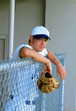 Baseball Waiting Game. Young man leans over the gate of the dugout at a baseball game. He is holding a ball glove. His uniform is white with blue trim royalty free stock photo