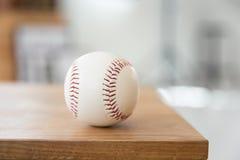 Baseball on wooden seat. Closeup Stock Photo