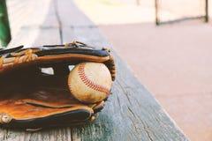 Baseballa sezon pokazuje rękawiczkę na ławce obraz royalty free