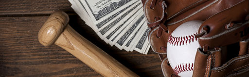 Baseballball, -handschuh, -schläger und -geld auf Holztisch Lizenzfreies Stockbild