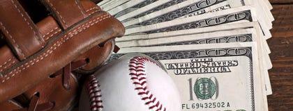 Baseballball, -handschuh und -geld auf Holztisch Stockbilder