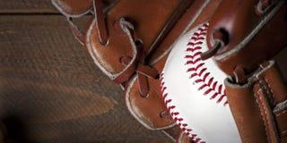 Baseballball, -handschuh und -schläger auf Holztisch Stockbilder