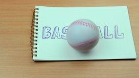 Baseballboll och anteckningsbok arkivfilmer