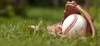 Baseballboll och handske på grönt gräs Fotografering för Bildbyråer