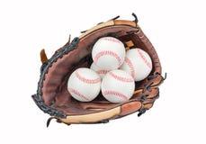 Baseballhandschuh mit vier Baseball Stockfoto