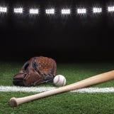 Baseballhandschuhball und -schläger nachts unter Stadion beleuchtet Lizenzfreie Stockfotos