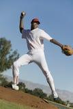 Baseballkanna som kastar bollen under leken Arkivbild