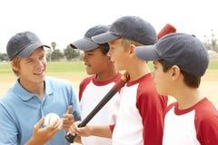 baseballpojkar arbeta som privatlärare åt lagbarn Fotografering för Bildbyråer