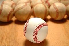 Baseballs. New baseballs in front of group of old worn baseballs - selective DOF stock photo