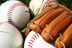 Baseballs and Glove. A baseball glove surrounded by balls on a field Stock Image