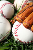 Baseballs and Glove. A baseball glove surrounded by balls on a field Stock Images