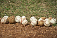 Baseballs. Lots of baseballs lined up along the ground Royalty Free Stock Photos