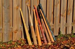 Baseballschläger, die auf einem Zaun sich lehnen lizenzfreie stockbilder
