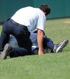 Basebalverletzung - Kursleiter neigt zum Spieler Stockbild