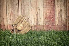 Basebol e bastões do vintage na grama perto da cerca de madeira velha Fotografia de Stock
