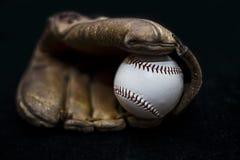 Basebol em uma luva com fundo preto Fotos de Stock Royalty Free