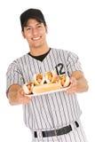 Basebol: Jogador que guarda a placa dos cachorros quentes imagens de stock royalty free