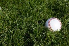 Basebol na grama Imagem de Stock Royalty Free