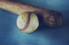 Basebol velho e bastão do vintage contra o fundo azul da textura imagem de stock