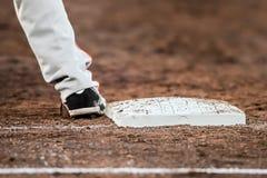Basebollspelaren med är han fot som trycker på grundplattan Arkivbilder