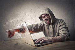 Based technology. Man furious with his fist smashing a computer royalty free stock image