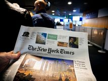 POV Reading The New York Times. BASEL, SWITZERLAND - NOV 11, 2017: Businessman in POV reading the New Yourk Times newspaper in the waiting queue lounge at royalty free stock photos