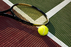 Baseline. An angled view of a tennis ball and racquet on the baseline of a tennis court stock photos