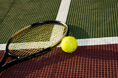 Baseline. A tennis ball and racquet laying on the baseline of a tennis court Stock Images