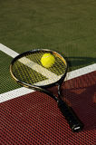 Baseline. A tennis ball and racquet on the baseline of a tennis court - Vertical crop stock image