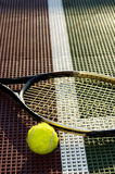 Baseline Long View. A vertical shot of a tennis ball and racquet on the baseline of a tennis court royalty free stock image