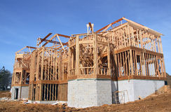 Basement Brick Wall. House being built in wooden frame with outer basement brick wall exposed stock photography
