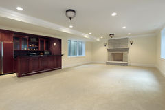 Basement with fireplace and bar. Basement in new construction home with bar and fireplace Stock Image