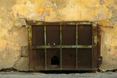 Basement of an old building with falling plaster covered with rusty grid. Street level window block with grid. royalty free stock photos