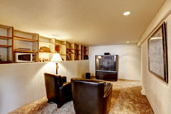 Basement room with tv and two leather chairs Stock Photo