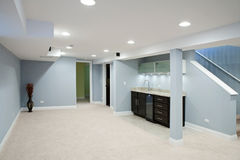 Basement with stone counter tops and carpet floor.