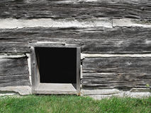 Basement window in old log building. Royalty Free Stock Photo